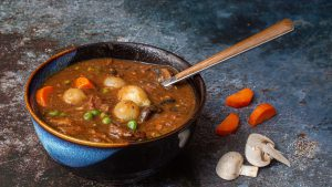 Flavorful beef stew with mushrooms carrots pearl onions peas in bowl with spoon