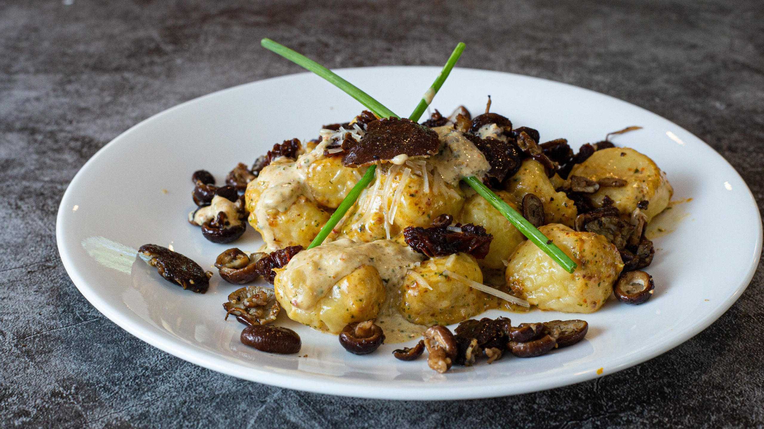Gnocchi with a sun-dried tomato pesto cream sauce garnished with parmesan cheese and chives