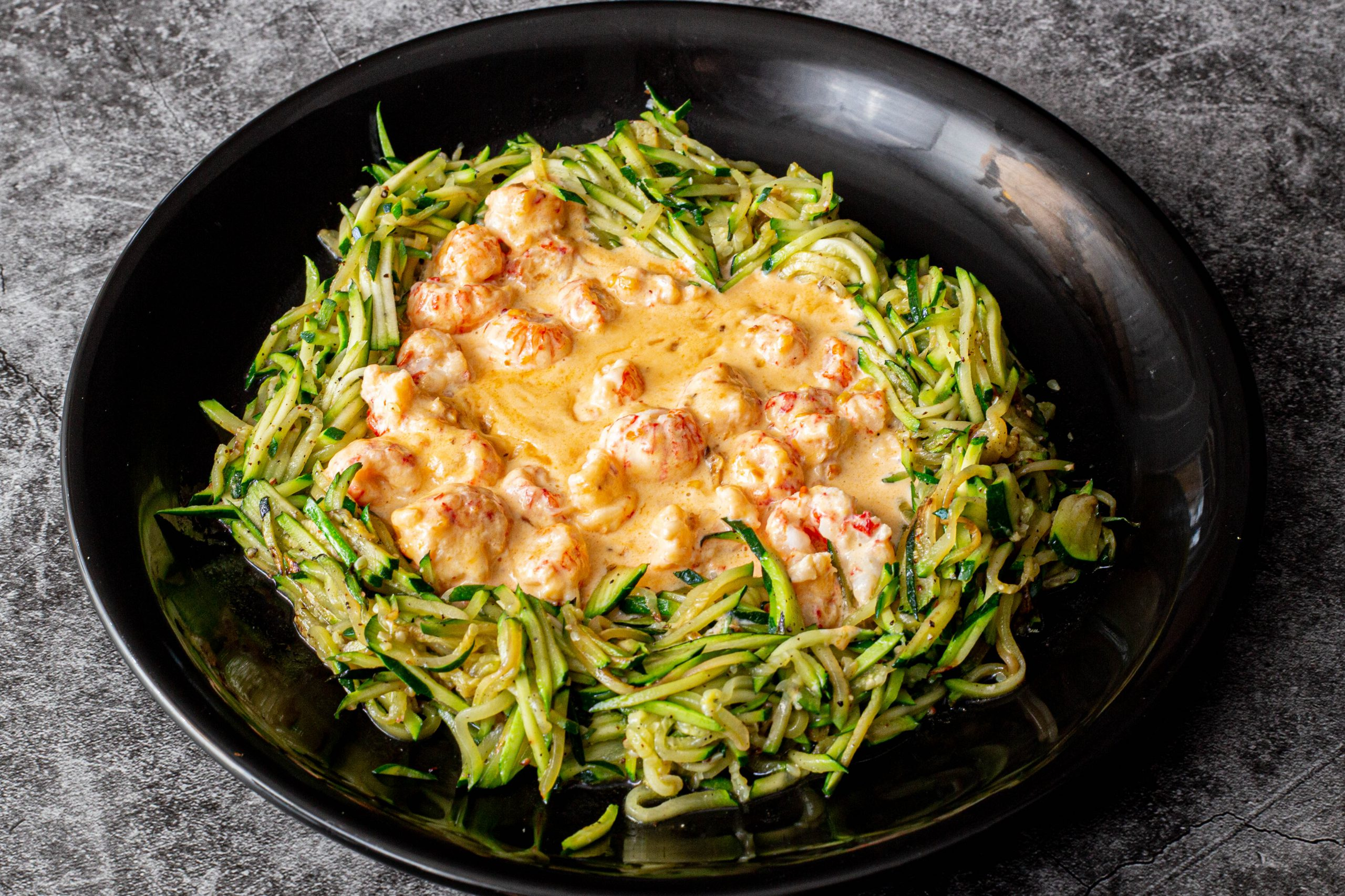 Shrimp in a spicy chili cream sauce on bed of zoodles, or zucchini noodles
