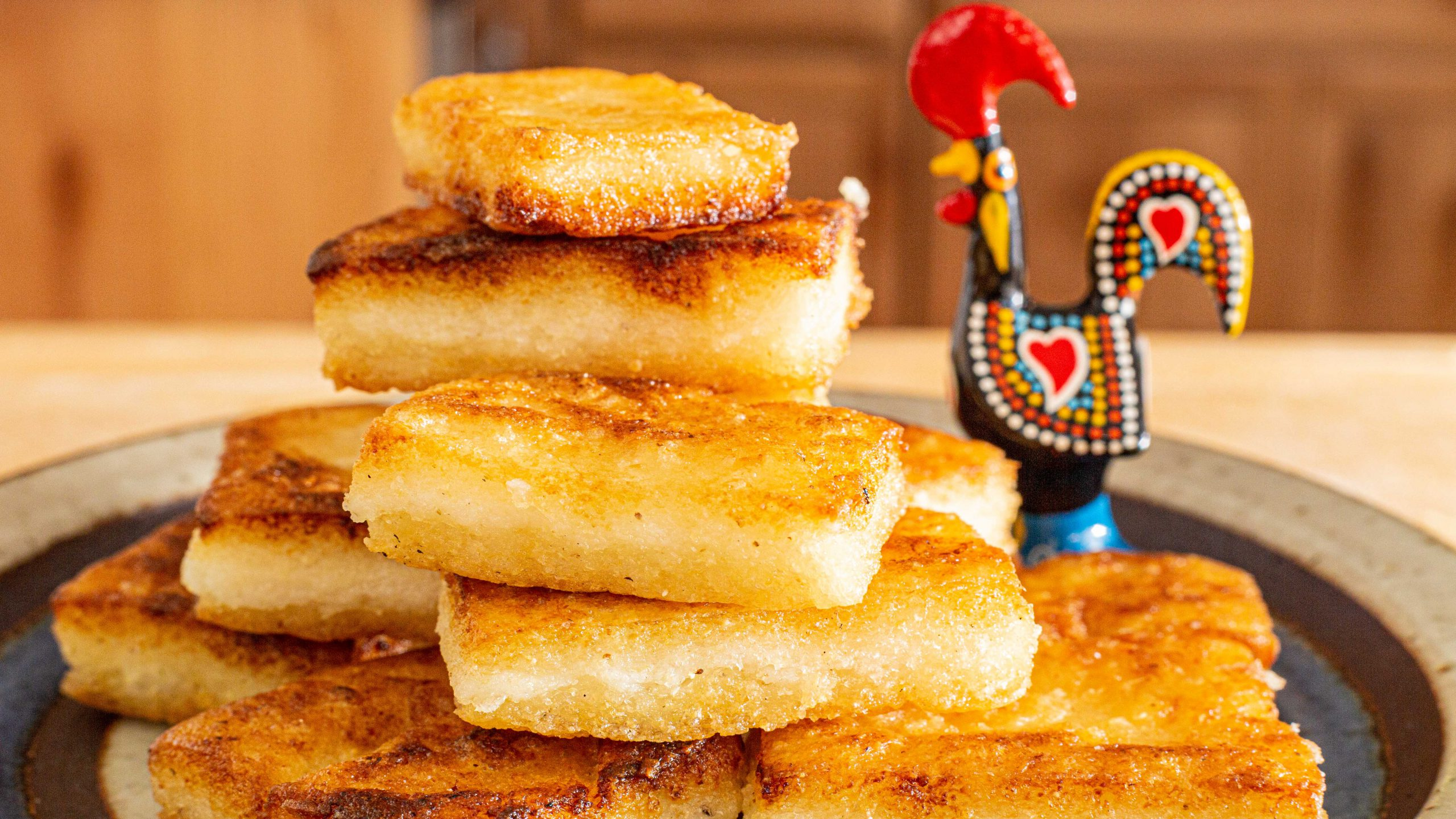 Portuguese Milho Frito, or fried cornmeal polenta, cut into small rectangles stacked on ceramic plate with small Portuguese rooster figurine