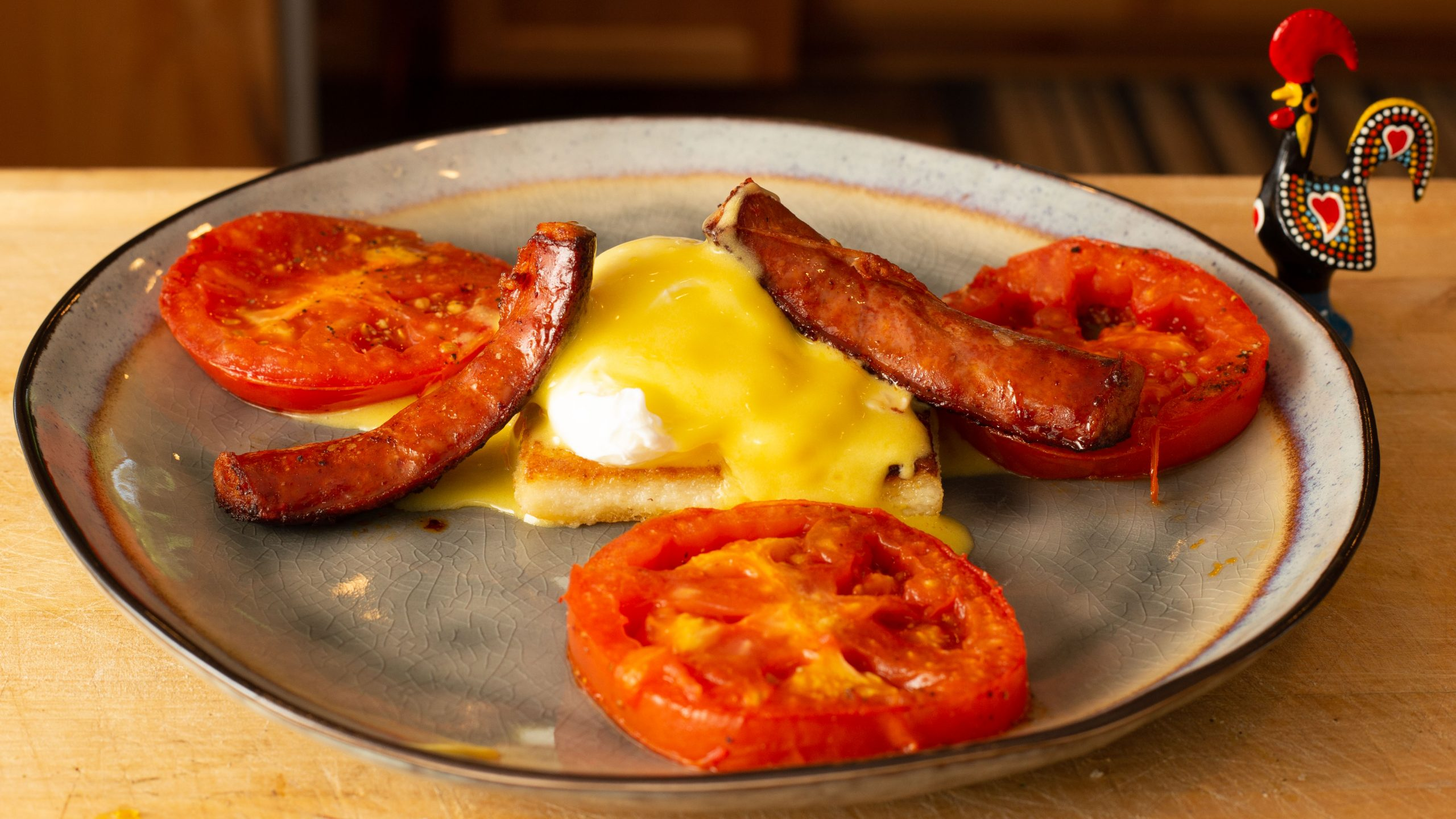 Portuguese Style Eggs Benedict with milho frito, poached eggs, tomato and linguica sausage
