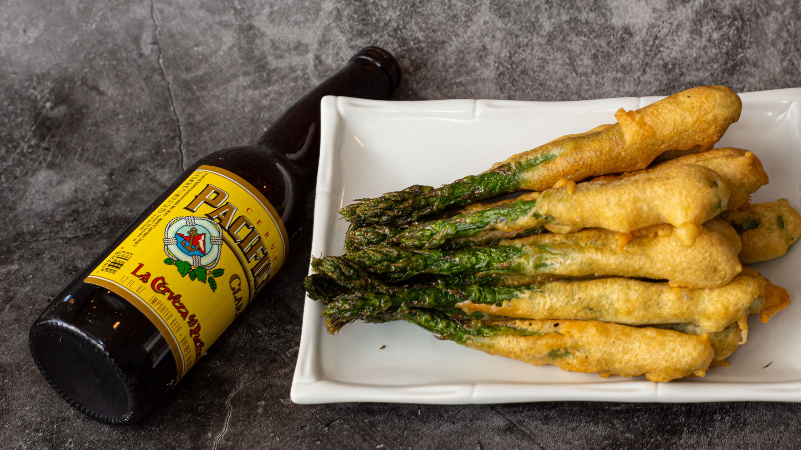 Beer battered asparagus on plate beside a bottle of beer
