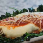 Chicken parmesan topped with melted cheese, marinara sauce and surround by sauteed spinach