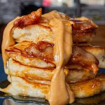 Stack of pancakes topped with bacon, peanut butter and maple syrup