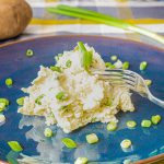 Perfect mashed potatoes topped with green onions on ceramic plate