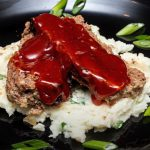 Meat loaf topped with glaze on top of mashed potatoes