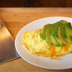 Omelet filled with sausage, topped with avocado and shredded cheese