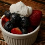 Marinated blueberry, strawberry dessert topped with whipped cream