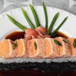 Seared salmon nigiri sushi atop sushi rice and nori