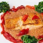 Sauteed salmon surrounded by a tomato coulis sauce with spinach bordering plate