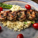 Grilled shrimp skewered on rosemary sprig over couscous