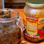 Sun-Dried tomato pesto beside a jar of sun-dried tomatoes in olive oil