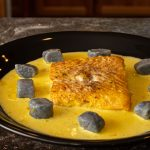 Halibut in a saffron cream sauce surrounded by purple potato gnocchi