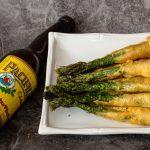 Beer battered asparagus on plate beside a bottle of beer
