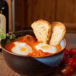 Bowl of tomato and onion soup with poached eggs and crusty bread from Madeira Island Portugal