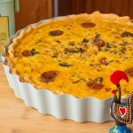 Portuguese Quiche, in pie pan with Portuguese rooster in foreground and pie weight box in background
